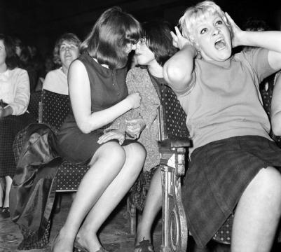 Duas garotas trocam carícias durante um show dos Beatles em 1964
