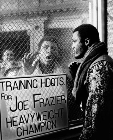 """O boxeador Muhammad Ali zomba de seu adversário Joe Frazier antes do confronto que seria considerado """"A luta do século"""", em janeiro de 1974"""