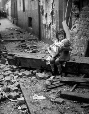 Uma criança britânica conforta sua boneca em meio a destroços de sua casa, destruída por bombardeios alemães em 1940