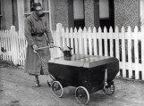 Mulher usa máscara e leva bebê em carrinho resistente a gases na Inglaterra em 1938