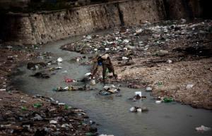 Homem recolhe  água em rio coberto de lixo, em Porto Príncipe (foto: Emilio Morenatti/AP)